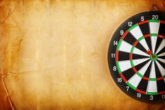 Vintage dart board on dark wall Royalty Free Stock Photos