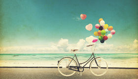 Vintage de bicyclette de F avec le ballon de coeur sur le ciel bleu de plage Images libres de droits