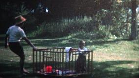 (vintage de 8m m) mamá 1966 que tira del niño a través del césped mientras que está enjaulado almacen de video