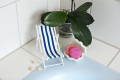 A vintage decorations beach chair for relaxing is standing near swimming pool or bath, seashells, soap, solid shampoo, soap dish. On a background is orchid royalty free stock image