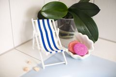A vintage decorations striped beach chair for relaxing is standing near swimming pool or bath, seashells, soap, solid shampoo,. Soap dish. on a background is stock photos