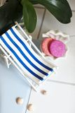A vintage decorations striped lounge for relaxing is standing near swimming pool or bath, seashells, soap, solid shampoo, soap. Dish. on a background is orchid royalty free stock photo