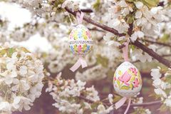 Vintage Decorative Easter egg hanging on flowering cherry tree with white flowers. Easter banner background royalty free stock image