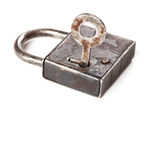 Vintage design closed iron padlock. key in hole Stock Image