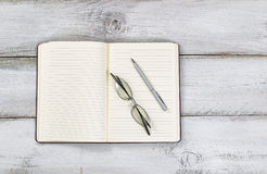 Vintage desktop with office stationery and reading glasses on ru Stock Images