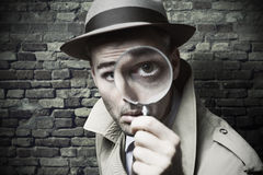 Vintage detective looking through a magnifier. Funny vintage detective looking through a magnifier royalty free stock photo