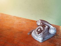 Vintage dial telephone on wooden brown table. Close up broken vintage dial telephone on wooden brown table, vintage filter effect Royalty Free Stock Photos