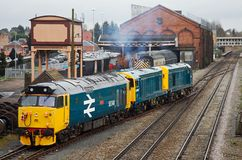 Vintage diesel lineup of locos. KIDDERMINSTER, UK - MARCH 29: A vintage class 50 diesel loco joins the mainline system hauled by an equally vintage pair of class Royalty Free Stock Photos