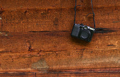 Vintage digital compact photo camera hanging on a wooden wall Royalty Free Stock Photos