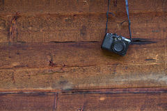 Vintage digital compact photo camera hanging on a wooden wall Stock Images