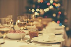 Vintage dining table set for Christmas dinner. Dining table full of a variety of delicious festive food and wine with a Christmas tree in the background in home Stock Images