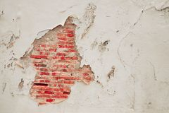 Vintage dirty cracked wall background : cracked cement can see red bricks texture inside Stock Images