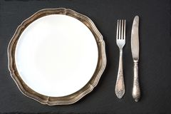 Vintage dish with silverware on slate background. Table place setting. Royalty Free Stock Photography