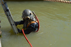 Vintage Diver. Submergence of vintage industrial diver in water royalty free stock photo