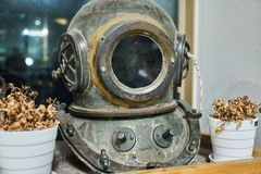 Vintage diving helmet displayed on a shelf with dry flowers on both sides. royalty free stock photography
