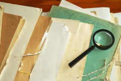 Vintage documents with magnifying glass Stock Photos