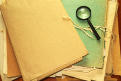 Vintage documents with magnifying glass Royalty Free Stock Photo