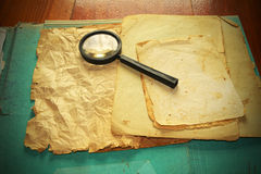 Vintage documents with magnifying glass Stock Photo