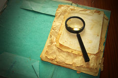 Vintage documents with magnifying glass Royalty Free Stock Images