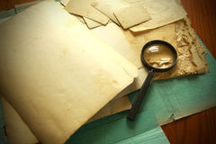 Vintage documents with magnifying glass Royalty Free Stock Photography
