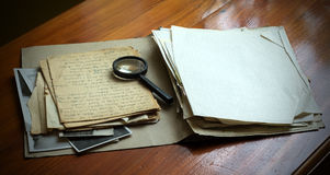 Vintage documents with magnifying glass Royalty Free Stock Photos
