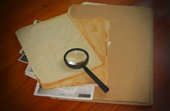 Vintage documents with magnifying glass Royalty Free Stock Image