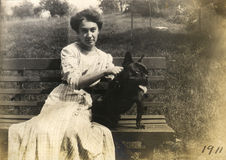 Vintage Dog Owner. Vintage portrait of a young woman and her black dog sitting on a park bench. Circa 1911 print has scratches, artifacts, fading and Stock Image