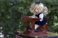 Vintage doll. Vintage baby doll in school uniform seated at desk, sold on flea market in Slovenia Royalty Free Stock Photo