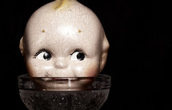 Vintage doll face on a glass cup Stock Image