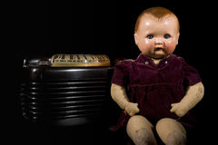 Vintage doll and radio. Vintage doll probably from the '30s sitting next to an old radio Royalty Free Stock Photo