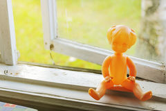 Vintage doll on the window sill Royalty Free Stock Photo