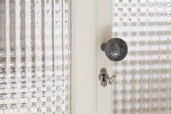 Vintage door handle on closed glass door royalty free stock photography