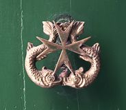 Vintage Door Knob Featuring The Maltese Cross And Two Dolphins O. N A Green Door stock image