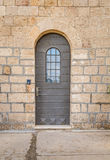 Vintage door with metal belts and rivets and barred window, Stella Maris Monastery in Haifa Stock Image
