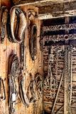 Vintage Draft Horse Harness Gear in Old Tack Room. Vintage draft horse harness gear and equipment on wood plank wall in an old barn tack room on a rural farm stock photos