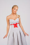 Vintage dress. Young beautiful and graceful girl in a white vintage cocktail dress with black polka dots with a neckline and a red bow at the waist on a gray Stock Photos