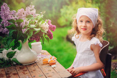 Vintage dressed child girl decorating cakes with flowers on garden tea party in spring Royalty Free Stock Photos