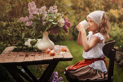 Vintage dressed child girl on garden tea party in spring. Happy vintage dressed child girl decorating cakes with flowers on garden tea party in spring Stock Photos