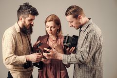 Vintage dressed company of photographers on busy faces working with with old camera. Fashion Photographer with old film royalty free stock photo