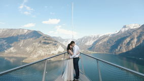 The vintage dressed couple is hugging while travelling on the boat at the background of the pure mountains.