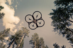 Vintage drone shot. A small spy quad copter scout drone flying through the trees in a forest stock photography