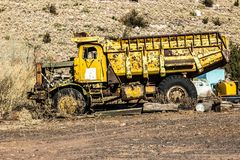 Vintage Dump Truck In Salvage Yard. Vintage Rusted & Pitted Yellow Dump Truck In Salvage Yard Stock Photos