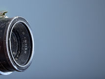 Vintage dusty 28 mm lens on blue   background Royalty Free Stock Image