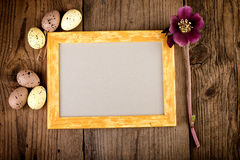 Vintage Easter background with picture frame on dark wooden board with copy space Stock Photography