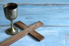 Vintage Easter cross and chalice of wine. On blue background Stock Photography