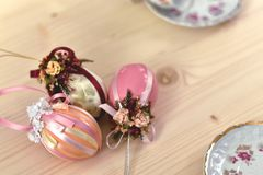 Vintage Easter decoration of three shiny pink coloured Easter eggs decorated with shiny ribbons stock images