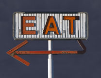 Vintage Eat Arrow Sign with Storm Sky. Vintage eat arrow sign in with dark storm sky Stock Images