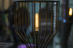 Vintage Edison lamp, floor long lamp in a black forged cage shade Stock Photography