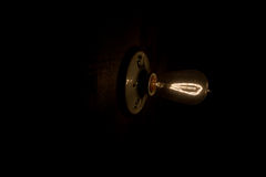 Vintage Edison Light Bulb. An old fashion bulb lit in a dark setting Stock Image