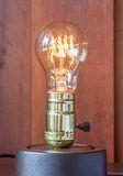 Vintage edison light bulb with wood background for hotel decorat Stock Images